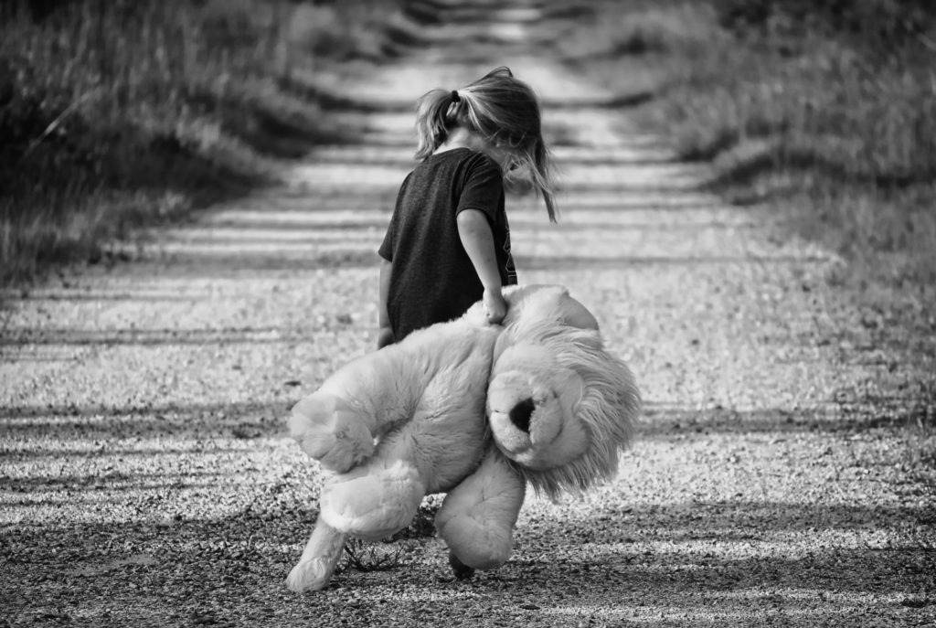 A lonely child of working couple dragging a teddy
